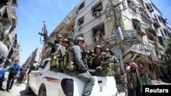 Policías sirios patrullan una calle de Duma, Siria, el 16 de abril.