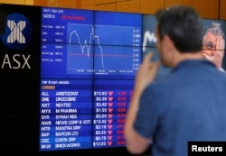 A man reacts in front of a board displaying stock prices at the Australian Securities Exchange (ASX) in Sydney, Australia, Nov. 9, 2016.