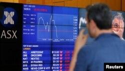 Seorang pria mengamati papan yang menampilkan harga-harga saham di Bursa Saham Australia (ASX) di Sydney, Australia (9/11).
