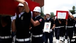Turkish police officers carry the coffin of slain police officers Serdar Kazar and Isa Ipek, killed in an attack by Kurdish rebels overnight, in the the city of Adana, southern Turkey, July 31, 2015.