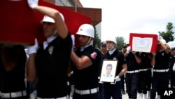 FILE - Turkish police officers carry the coffin of slain police officers Serdar Kazar and Isa Ipek, killed in an attack by Kurdish rebels overnight, in the the city of Adana, southern Turkey, July 31, 2015.
