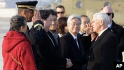 U.S. Vice President Mike Pence, right, and U.S. Gen. Vincent Brooks, commander of the United Nations Command, U.S. Forces Korea and Combined Forces Command, salute each other upon Pence's arrival at Osan Air Base in Pyeongtaek, South Korea, Feb. 8, 2018.