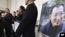 ຮູບຂອງທ່ານ Liu Xiaobao ນັກເຄື່ອນໄຫວເພື່ອສິດທິມະນຸດຈີນທີ່ ໄດ້ຮັບລາງວັນໂນແບລຂະແໜງສັນຕິພາບ ປະຈຳປີ 2010 ທີ່ກຳລັງຖືກຈຳຄຸກນັ້ນ ຕິດຢູ່ຂ້າງຝາບ່ອນທີ່ຜູ້ແທນສະພາຕໍ່າ ທ່ານ Christopher Smith ທີ່ມີພວກນັກເຄື່ອນໄຫວດ້ານສິດທິມະນຸດຈີນຕິດຕາມຢູ່ໃນຂະນະທີ່ທ່ານກ່າວຄຳປາໃສ ໃນກອງປ