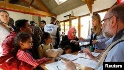 Photo: Des réfugiés de l'Irak et de la Syrie et de l'Irak parlent avec des médecins avant un contrôle médical après leur arrivée au centre Hubert Renaud à Cergy-Pontoise, près de Paris, France, le 9 septembre 2015. REUTERS/Jacky NaegelenATTENTION EDITORS : FRENCH LAW REQUIRES THAT THE FACES OF MINORS ARE MASKED IN PUBLICATIONS - RTSB2V