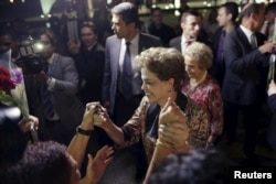 FILE - Brazil's President Dilma Rousseff greets women during a rally in support of her and against her impeachment in front of Planalto Palace in Brasilia, April 19, 2016.