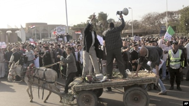 Protesters shout slogans from a donkey cart during a rally against the formation of a constituent assembly tasked with drafting a new constitution outside the Cairo convention center, March 24, 2012.