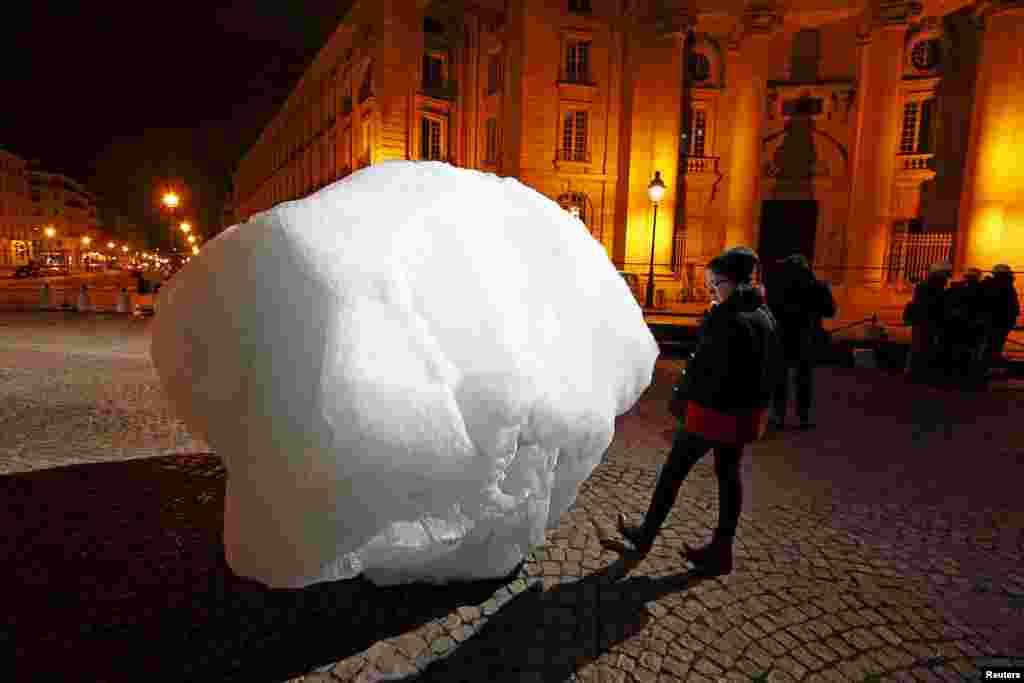 ស្រ្តីម្នាក់ឈរមើលបណ្តុំទឹកកកមួយ ដែលប្រមួលយកមកពីតំបន់ Greenland នៅអំឡុងពេលរៀបតាំងមួយនៅ Place du Pantheon សម្រាប់គម្រោងមួយហៅថា Ice Watch Paris នៅទីក្រុងប៉ារីស ប្រទេសបារាំង។