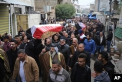Mourners carry the Iraqi-flag-draped coffins of bomb victims Arif Muhanad, 36, and his son, Muhanad, 8, during their funeral procession in Baghdad, Iraq, Dec 31, 2016. A pair of bomb blasts targeting a market Saturday in central Baghdad killed and wounded many people, officials said.