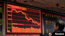 FILE - An investor watches a board showing stock information at a brokerage office in Beijing, China, Oct. 8, 2018.
