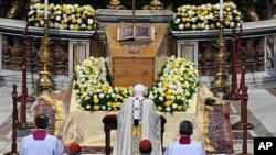 Pope Benedict XVI kneels in front of the coffin of the late Pope John Paul II inside St. Peter's Basilica at the Vatican, May 1, 2011