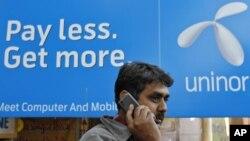 Một người đàn ông Ấn Ðộ nói chuyện bằng điện thoại di động phía trước một bảng quảng cáo của hãng Uninor tại một khu chợ ở Ahmedabad, ngày 6/2/2012