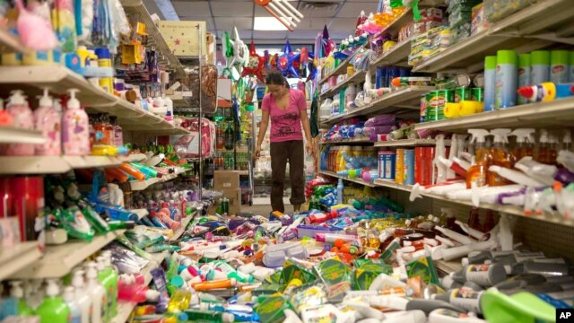 Nina Quidit cleans up the Dollar Plus and Party Supplies Store in American Canyon, California, after a major earthquake, Aug. 24, 2014.