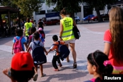 "Volunteers escort refugee children at the volunteer-run ""Refugee Education Chios"" school on the island of Chios, Greece, Sept. 7, 2016."