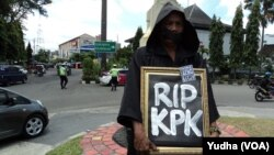 "Seorang peserta aksi keprihatinan di Solo mengenakan pakaian dan kerudung hitam sambil membawa tulisan ""RIP, KPK"", 3 Maret 2015 (Foto: VOA/Yudha)"