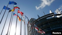 FILE - Flags of European Union member states fly in front of the European Parliament building in Strasbourg, France, April 15, 2014.