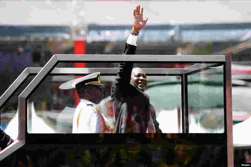 Kenya's President Uhuru Kenyatta waves upon his arrival to his inauguration ceremony where he will be sworn in as president at Kasarani Stadium in Nairobi.