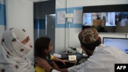 FILE - A Pakistani paramedic checks a child at a telemedicine center run by the government of Khyber Pakhtukhwa in the remote Behali area, Oct. 20, 2017. Singapore has introduced telemedicine legislation as part of its Healthcare Services Act 2020.
