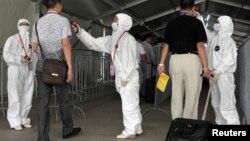 为防埃博拉,人们在进入广交会前接受体温检查。