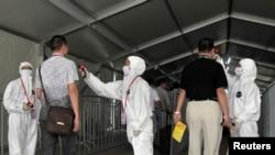 人們在進入廣交會會場前接受體溫檢查,以防伊波拉(2014年10月23日)