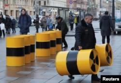 Karyawan pusat perbelanjaan memindahkan tong selama piket yang diadakan oleh aktivis Greenpeace untuk memprotes impor limbah radioaktif ke Rusia untuk disimpan di Saint Petersburg, Rusia 17 Desember 2019. (REUTERS/Anton Vaganov)