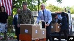美國副總統邁克·彭斯(Mike Pence)在維吉尼亞州亞歷山大市的伍德賓康復和醫療中心(Woodbine Recovery And Healthcare Center)移動一輛手推車,車裡裝著來自聯邦應急管理局(FEMA)的一箱箱個人防護用品。 (2020年5月7日)