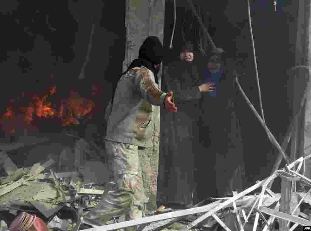 Một người đàn ông chỉ đường cho 2 người phụ nữ Syria khi rời khỏi tòa nhà sau vụ tấn công được cho là cuộc không kích của lực lượng chính phủ vào thành phố Aleppo ở phía bắc Syria.
