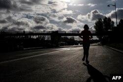 Seorang perempuan sedang jogging sepanjang Sungai Seine, 3 April 2019 di Paris. (Foto: AFP)