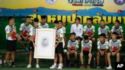 Coach Ekkapol Janthawong, left, and the 12 boys show their respect and thanks as they hold a portrait of Saman Gunan, the retired Thai SEAL diver who died during their rescue attempt, during a press conference in Chiang Rai, northern Thailand, Wednesday, July 18, 2018. (AP Photo/Vincent Thian)