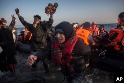 Refugees and migrants react as they disembark from a dinghy after their arrival from the Turkish coast to the northeastern Greek island of Lesbos on Nov. 17, 2015.