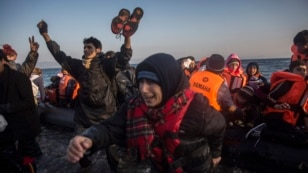 FILE: Refugees and migrants react as they disembark to the northeastern Greek island of Lesbos on Nov. 17, 2015.