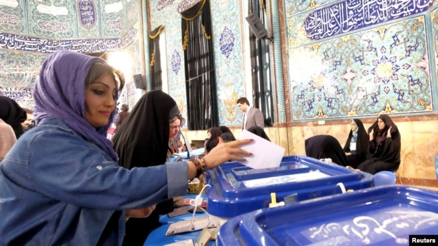 An Iranian woman casts her ballot during elections for the parliament and Assembly of Experts, which has the power to appoint and dismiss the supreme leader, in Tehran, Feb. 26, 2016.