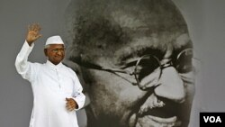 Aktivis Anna Hazare dengan latar belakang gambar Mahatma Gandhi di New Delhi. Gerakan anti-korupsi damai yang dipimpin Anna Hazare mendapatkan simpati dari rakyat semua kalangan dan kelompok usia di India.
