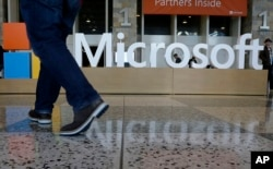 FILE - In this April 28, 2015 file photo, a man walks past a Microsoft sign set up for the Microsoft BUILD conference at Moscone Center in San Francisco.