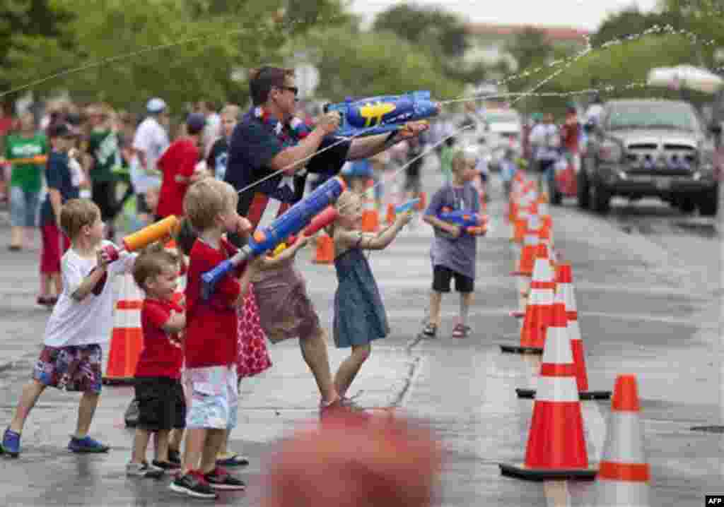 Spectators lining Nevada Way shoot water guns at passing floats during the 63rd Annual Boulder City Damboree Parade, Monday, July 4, 2011, in Boulder City, Nev. The last half of the parade entrants are called Water Entrees, making them fair game for water