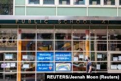 A pedestrian walks past Public School 41 following the outbreak of the coronavirus disease, New York.