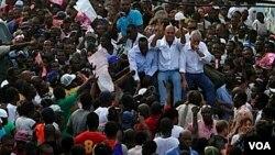 Kandidat presiden Haiti, Michel Martelly (tengah) ditemani kandidat lainnya, Charles-Henri Baker (kanan) dan musisi Wyclef Jean naik ke atas kendaraan yang berjalan melintasi jalanan kota Port-au-Prince untuk memrotes pemilu.
