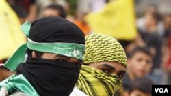 Palestinos celebran la reconciliación usando máscaras de Hamas (izquierda) y de Fatah (derecha).