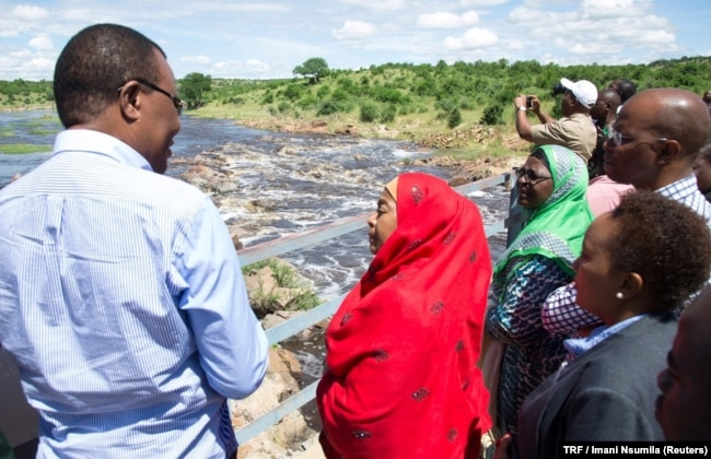 FILE - Tanzanian Vice President Samia Suluhu Hassan, in the red shawl, is briefed about the destruction of the Ruaha river, in Kilolo district, Tanzania, May 8, 2017.