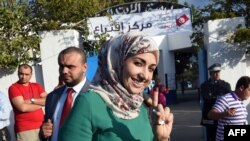 Soumaya Rached Ghannouchi shows her ink-stained finger after voting in the country's first post-revolution parliamentary election on October 26, 2014 in the Tunis suburb of Ben Arous.
