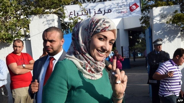 FILE – A voter shows her ink-stained finger after participating in Tunisia's first post-revolution parliamentary election in the Tunis suburb of Ben Arous, Oct. 26, 2014.