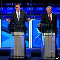 L'ancien gouverneur Mitt Romney répondant à une question tandis que le député Ron Paul écoute.