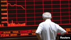 7일 중국 베이징에서 한 투자자가 증시 현황을 표시하는 전광판을 지켜보고 있다.