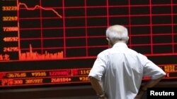 An investor watches an electronic board showing stock information at a brokerage office in Beijing, China, July 7, 2015.