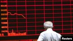 Seorang investor mengamati papan elektronik berisi pergerakan saham di sebuah kantor pialang saham di Beijing, China (7/7).