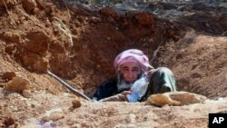 This citizen journalism image provided by Edlib News Network, ENN, which has been authenticated based on its contents and other AP reporting, shows an elderly Syrian rebel in a trench in Idlib province, June 12, 2013.
