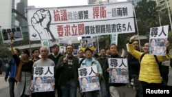 FILE - Demonstrators hold up portraits of five missing staff members of a publishing house and a bookstore during a protest over the disappearance of booksellers in Hong Kong, Jan. 10, 2016.