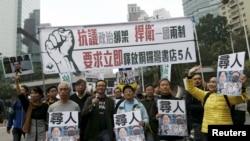 Para pengunjuk rasa membawa potret lima orang staf perusahaan penerbit dan toko buku yang hilang dalam sebuah aksi protes di Hong Kong, 10 Januari 2016 (Foto: dok).