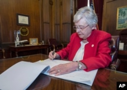 This photograph released by the state shows Alabama Gov. Kay Ivey signing a bill that virtually outlaws abortion in the state, May 15, 2019, in Montgomery, Ala.