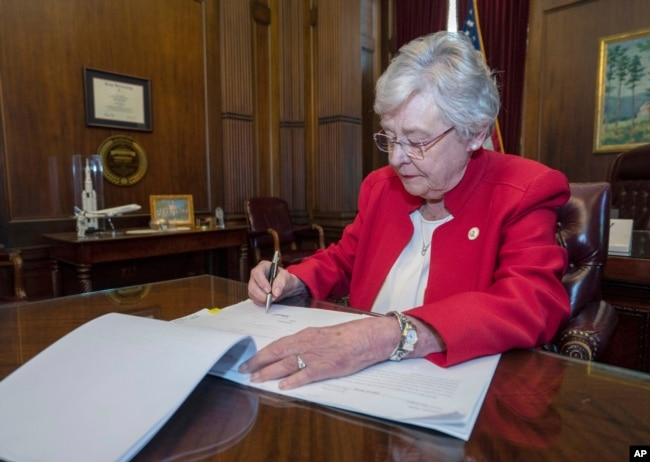 FILE - This photograph released by the state shows Alabama Gov. Kay Ivey signing a bill that virtually outlaws abortion in the state, May 15, 2019, in Montgomery, Ala.