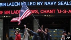 People celebrate outside the ABC studios in New York's Times Square as news of Osama bin Laden's death is announced on the ticker, Monday, May 2, 2011
